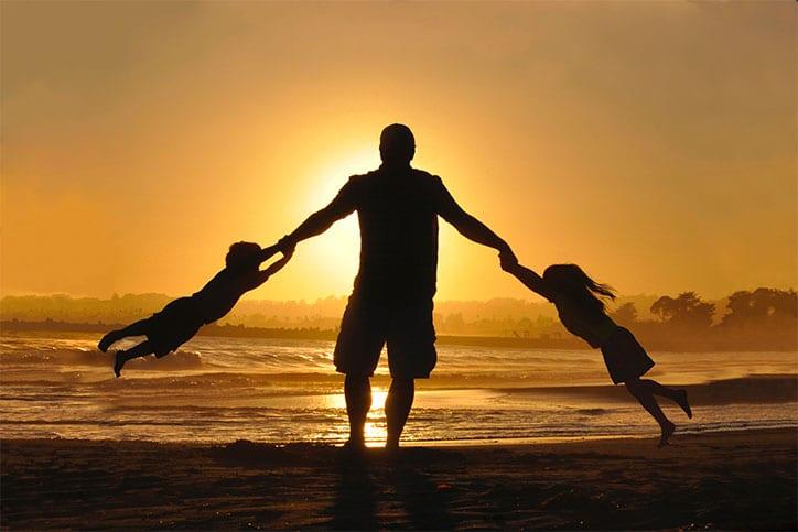Parent jouant avec ses enfants au coucher du soleil